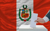 Man voting on elections in peru in front of flag — Foto Stock