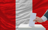 Man voting on elections in peru in front of flag — Foto de Stock
