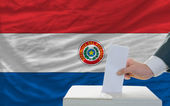 Man voting on elections in paraguay in front of flag — Foto de Stock