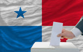 Man voting on elections in panama in front of flag — Foto de Stock
