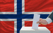Man voting on elections in norway in front of flag — Stok fotoğraf