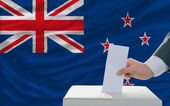 Man voting on elections in new zealand in front of flag — Stock Photo