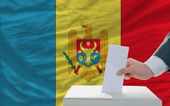 Man voting on elections in moldova in front of flag — Stockfoto