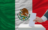 Man voting on elections in mexico in front of flag — Stockfoto