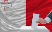 Man voting on elections in malta in front of flag — Stockfoto