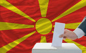 Man voting on elections in macedonia in front of flag — Foto de Stock