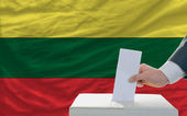 Man voting on elections in lithuania in front of flag — Foto de Stock
