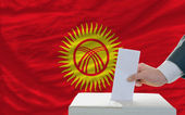 Man voting on elections in kyrghyzstan in front of flag — Stok fotoğraf