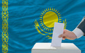 Man voting on elections in kazakhstan in front of flag — Stockfoto