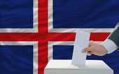 Man voting on elections in iceland in front of flag — Stockfoto