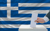 Man voting on elections in greece in front of flag — Stock Photo
