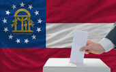 Man voting on elections in georgia in front of flag — Stock Photo