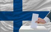Man voting on elections in finland in front of flag — Stok fotoğraf
