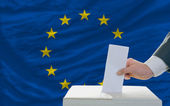 Man voting on elections in europe in front of flag — Stok fotoğraf