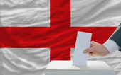 Man voting on elections in england in front of flag — Foto de Stock