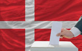 Man voting on elections in denmark in front of flag — Stockfoto