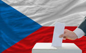 Man voting on elections in czech in front of flag — Stok fotoğraf