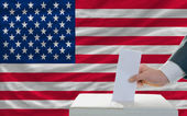Man voting on elections in america in front of flag — Stock Photo