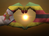 Heart and love gesture by hands colored in zimbabwe flag during — Stock Photo