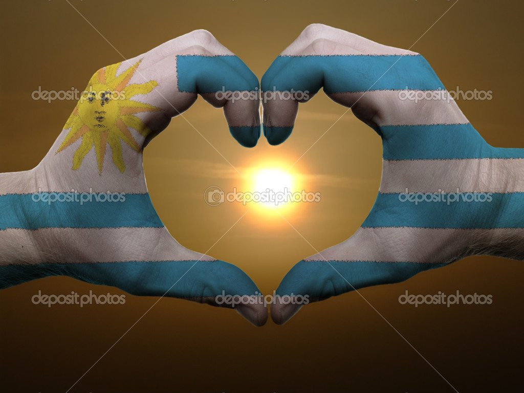 Gesture made by uruguay flag colored hands showing symbol of heart and love during sunrise  Stock Photo #7857196