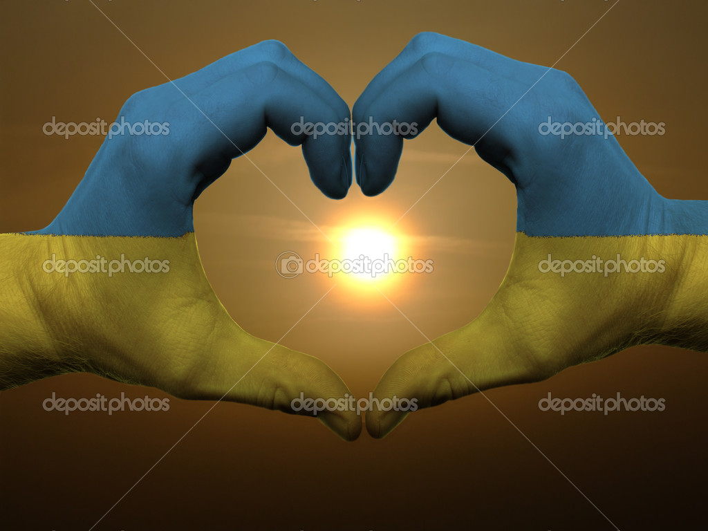 Gesture made by ukraine flag colored hands showing symbol of heart and love during sunrise  Stock Photo #7857204