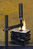 Burning stack of hard drive pressed together with clamp — Stock Photo