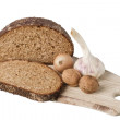 Brown bread on shelf with onion, garlic and walnut - Stock Photo