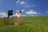 Woman At Desk With Computer Using Megaphone In Green Field — Stock Photo