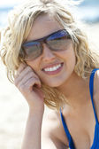 Beautiful Young Blond Woman in Sunglasses Smiling At The Beach — Stock Photo