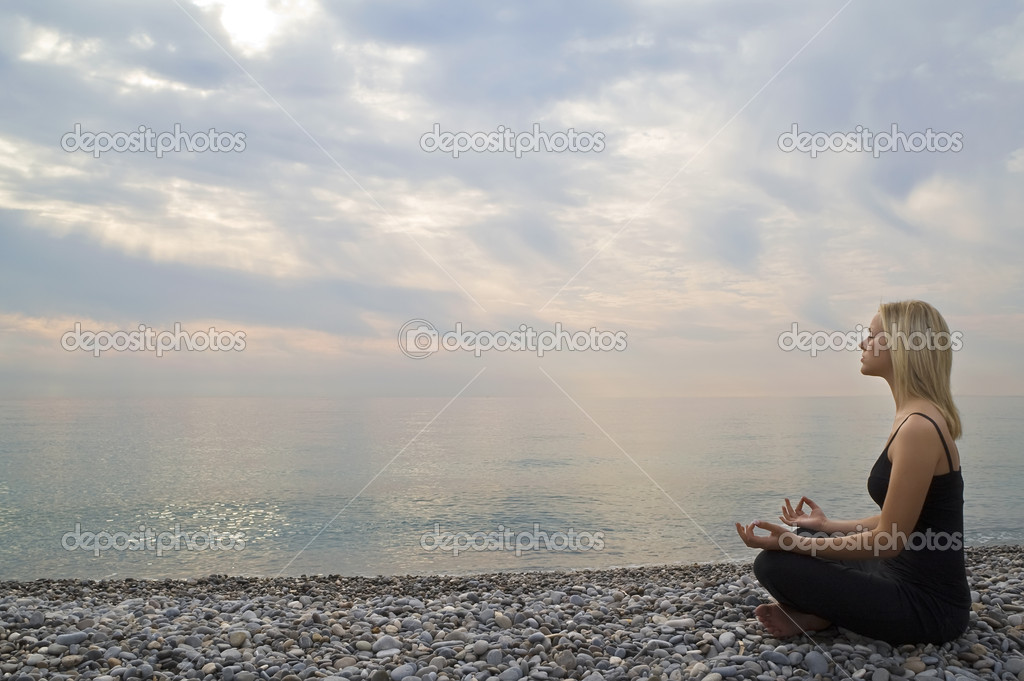 A beautiful young blond woman sitting cross legged in a yoga position on a beach at sunrise — Stock Photo #6778772