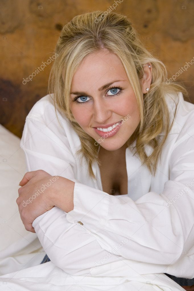 A stunningly beautiful blue eyed blonde haired young woman smiles into the camera while sitting on a bed and holding her knees  Stock Photo #6778842