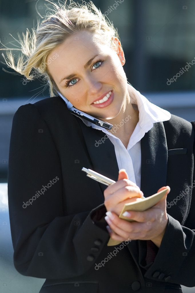 A stunningly beautiful young blond woman bathed in sunshine while on her mobile phone and making notes — Stock Photo #6779105