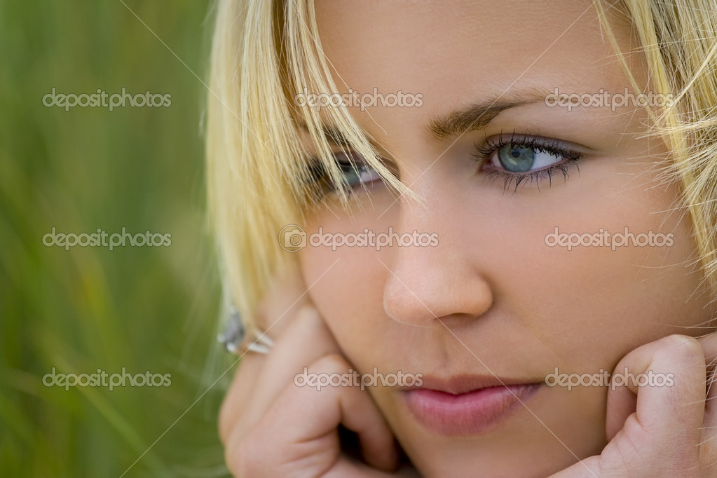A beautiful blond haired blue eyed model sits amid tall green grass  Stock Photo #6779106