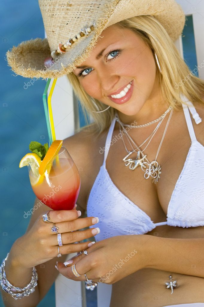 Stunningly beautiful young blond woman in straw cowboy hat and bikini enjoying a cocktail by a deep blue sea — Stock Photo #6779111