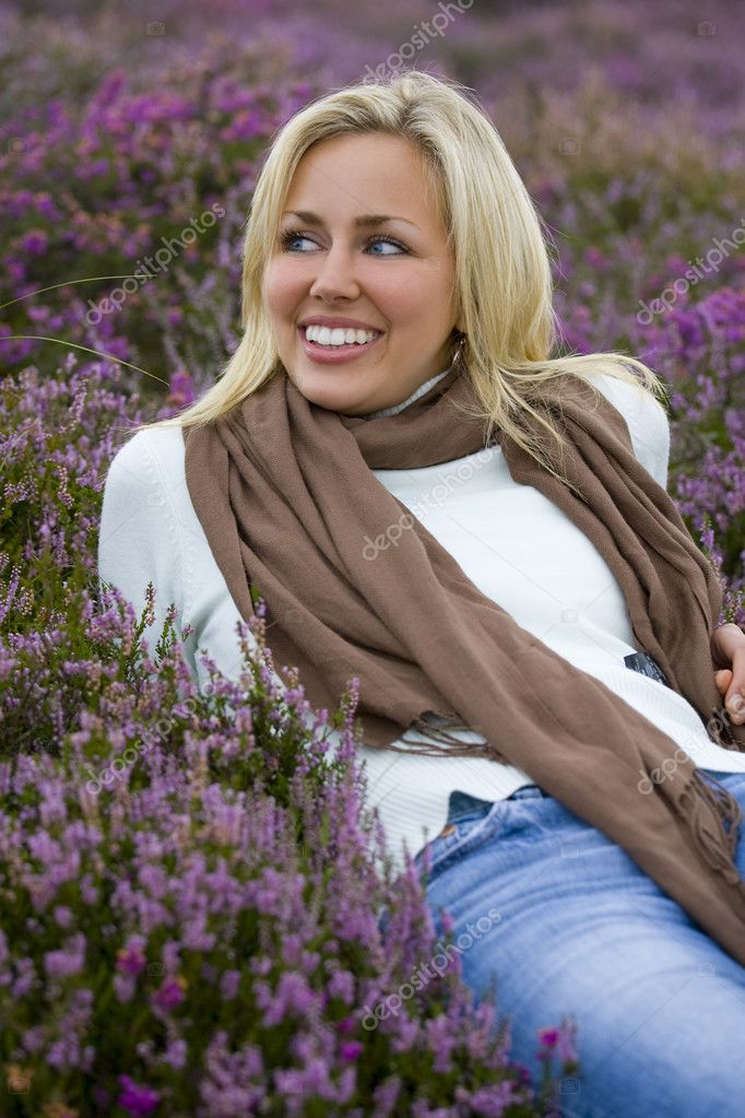 A beautiful blond haired blue eyed young woman laying amongst flowering heather and laughing  Stock Photo #6779145