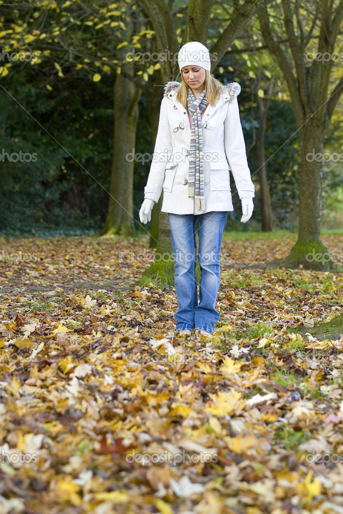 A beautiful young woman looking sad and standing alone in a leaf filled wood.  Foto de Stock   #6779180