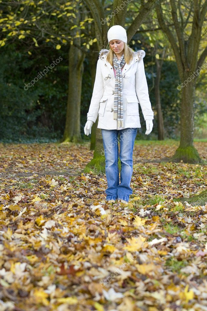 A beautiful young woman looking sad and standing alone in a leaf filled wood. — Stock fotografie #6779180