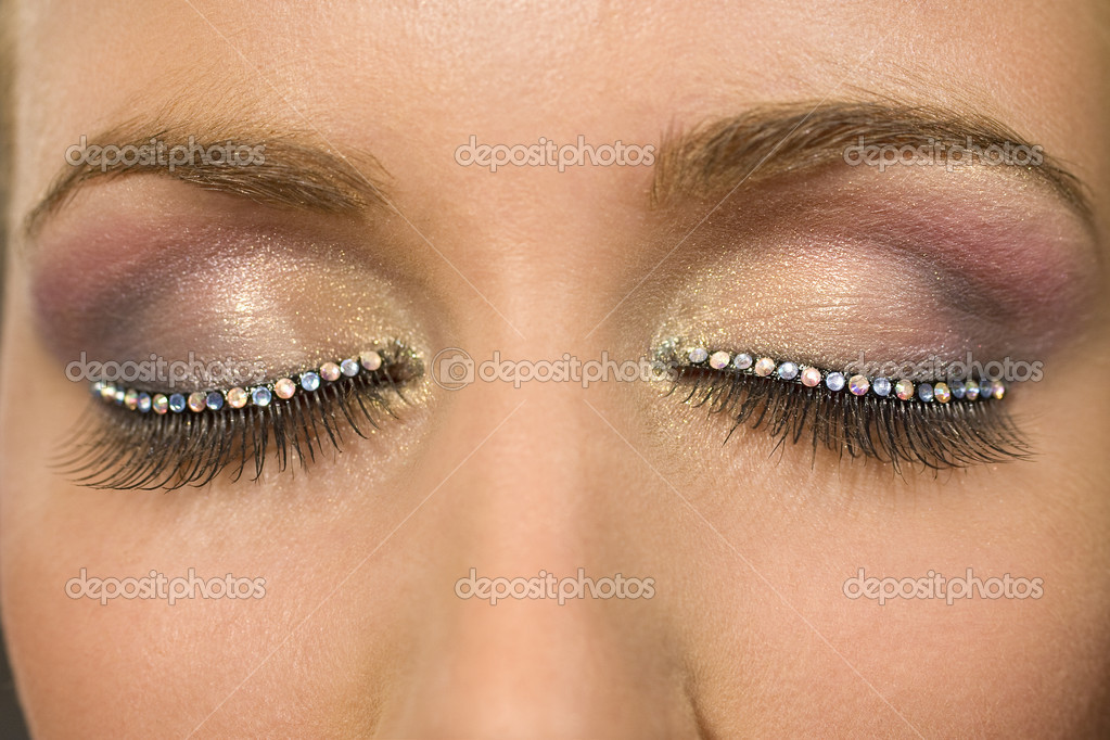 A macro close up of a beautiful woman's make up eye with jewelled false eyelashes — Foto Stock #6779192