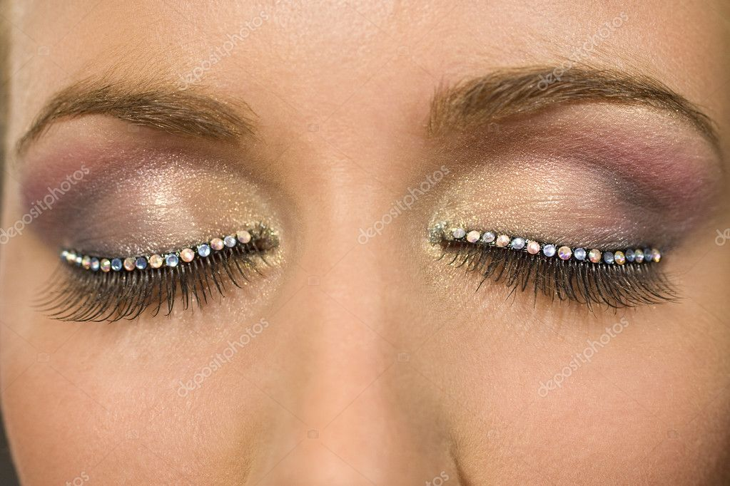 A macro close up of a beautiful woman's make up eye with jewelled false eyelashes — Zdjęcie stockowe #6779192