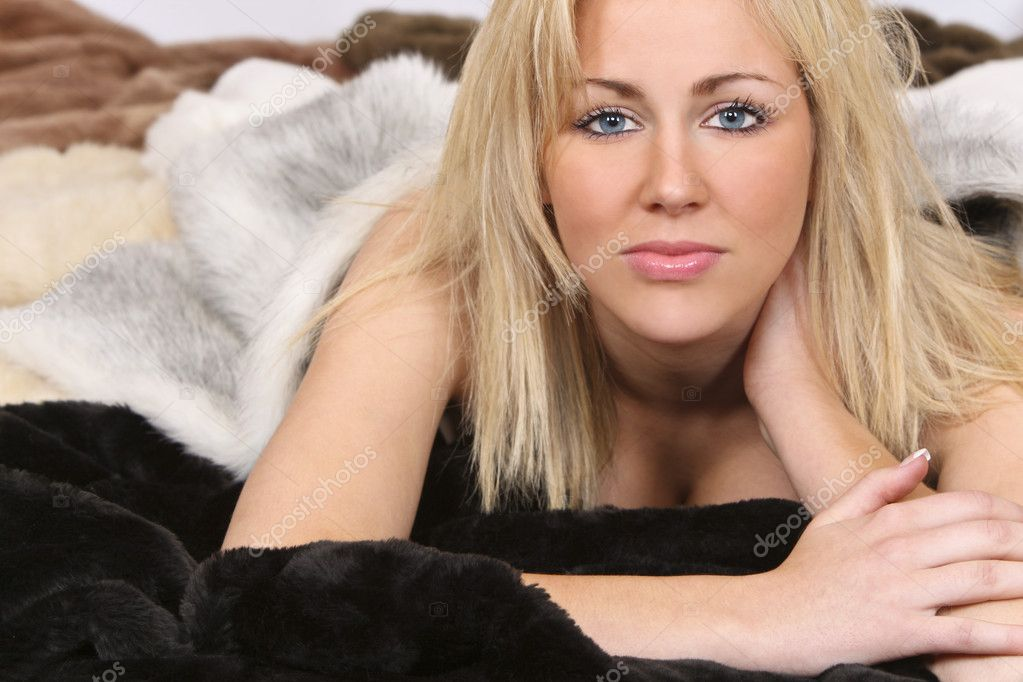 A beautiful young blond woman lying on a bed of (fake) furs — Stock Photo #6781711