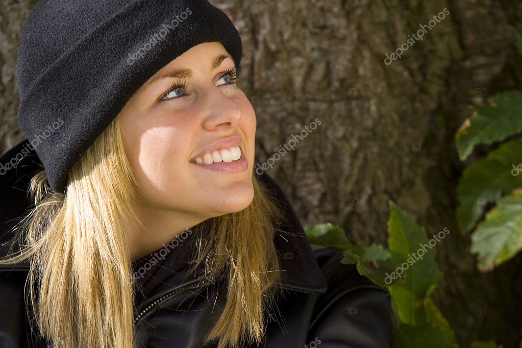 A beautiful young blonde woman in a black beanie hat and leather jacket smiles while leaning against a tree — Stock Photo #6781727
