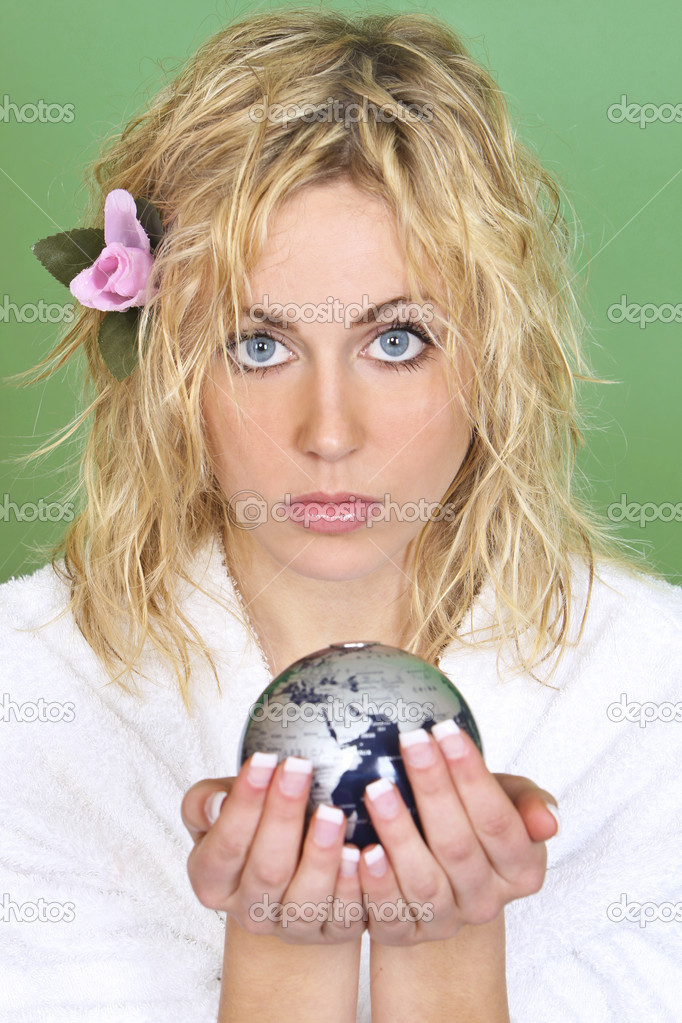 A beautiful young woman with blue eyes holds a globe while looking concerned - shot with a green background that could be used to convey green issues or relativ — Stock Photo #6781758