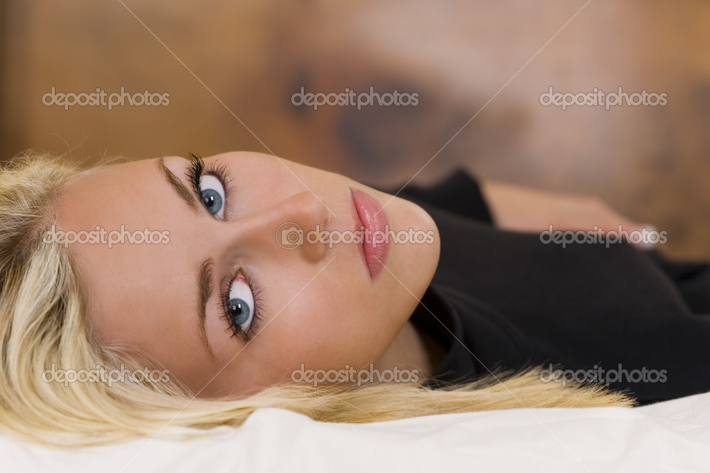 A gorgeous young blond woman with striking blue eyes laying down and looking thoughtfully into the lens. — Stock Photo #6790698