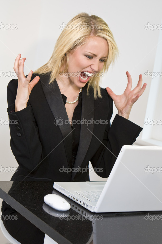 A beautiful young female executive expressing frustration at her laptop computer — Stock Photo #6790723