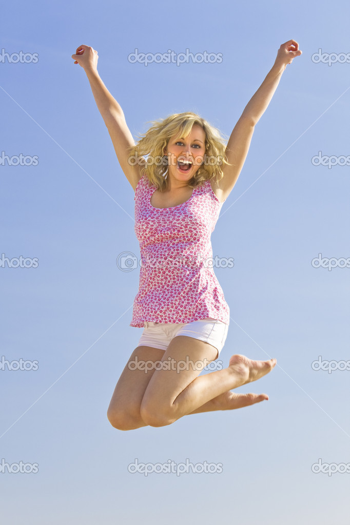 A beautiful young blond woman jumping high in the air with a big smile — Stok fotoğraf #6790744