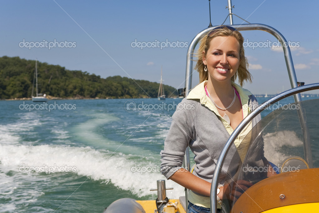 A stunningly beautiful young woman driving a speedboat and having fun with the Mediterranean coast and yachts in the background — Stock Photo #6790754