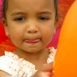 A young mixed race child holding balloons at a party — Stock Photo