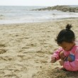 A young mixed race girl plays on a sandy beach — Stok fotoğraf