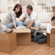 Stock Photo: Family Unpacking Boxes Moving House