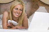 Yataklar beyaz dizüstü bilgisayar kullanan güzel genç kadın — Stok fotoğraf